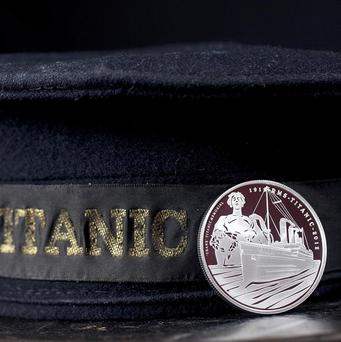 The Royal Mint's five pound coin rests against the cap of a surviving crew-member from the Titanic