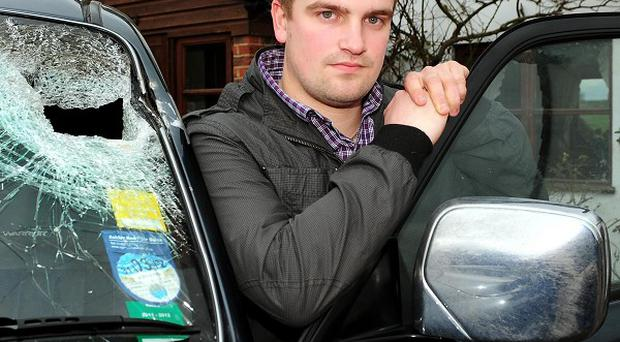 Callum Jackson next to his damaged car at home in Stoulton, Worcestershire