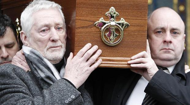 Actor David Kelly's son David, right, carries his coffin during his funeral at the Church of the Miraculous Medal in Clonskeagh, Dublin