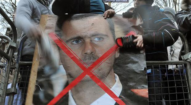 Protesters beat a poster of President Assad with their shoes outside the Syrian Embassy in London as a bloody uprising continues in the country