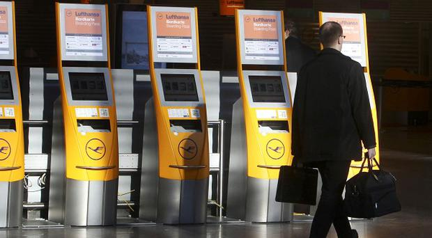 A man walks along empty check-in counters at Frankfurt airport which has has been hit by a strike (AP)