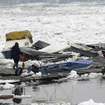 A man walks near damaged boats on a frozen part of the Danube in Belgrade (AP)