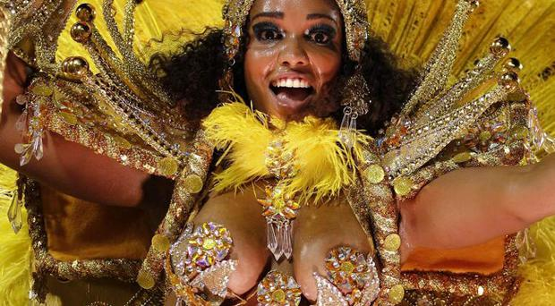 A dancer of Sao Clemente samba school parades on a float during carnival celebrations at the Sambadrome in Rio de Janeiro, Brazil, Monday, Feb. 20, 2012.