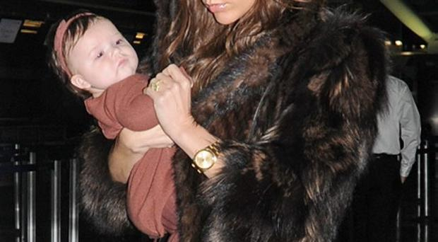 Tiring work: Victoria Beckham is juggling looking after baby Harper with launching new fashions