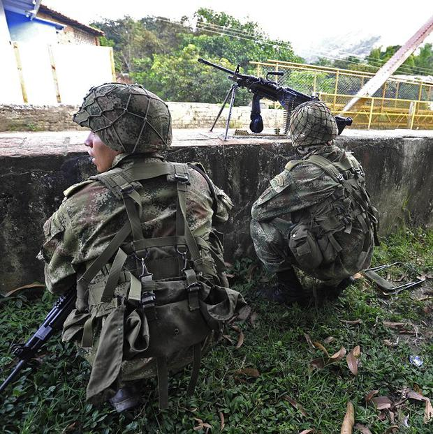 Soldiers take cover during fighting with leftist rebels in Caloto, southern Colombia (AP/Carlos Julio Martinez)