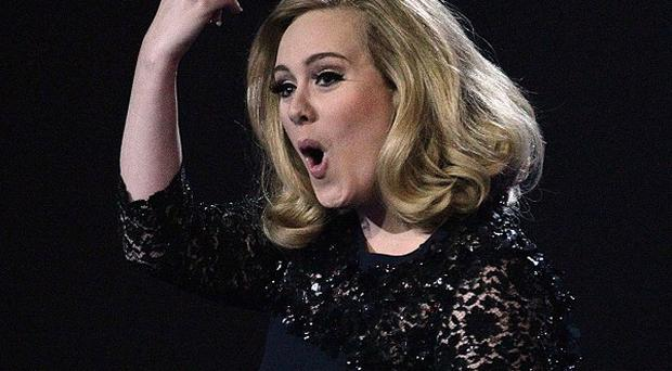 Adele gestures after collecting her award for Album of the Year during the Brits