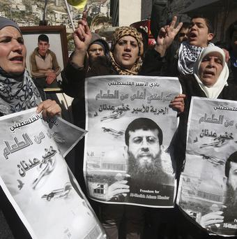 Palestinians hold posters during a demonstration in solidarity with Khader Adnan who has been on hunger strike for two months (AP Photo/Nasser Ishtayeh)