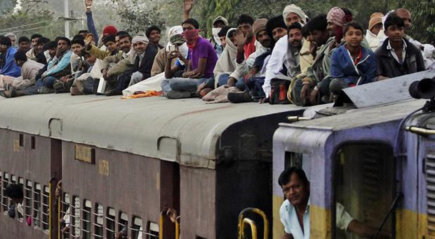 Passengers sit on the roof of a train as it leaves Junagadh station (AP)