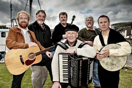 Left to right: George Millar, John Reynolds, Sean O'Driscoll, Wilcil McDowell (seated), Ian Millar, Fred Graham at Carnlough Harbour, N. Ireland. George Millar and his cousin Ian Millar are from Ballymena, original member Wilcil McDowell is from Larne, Sean O'Driscoll is from Cork, and both John Reynolds and percussionist Fred Graham are from Belfast.