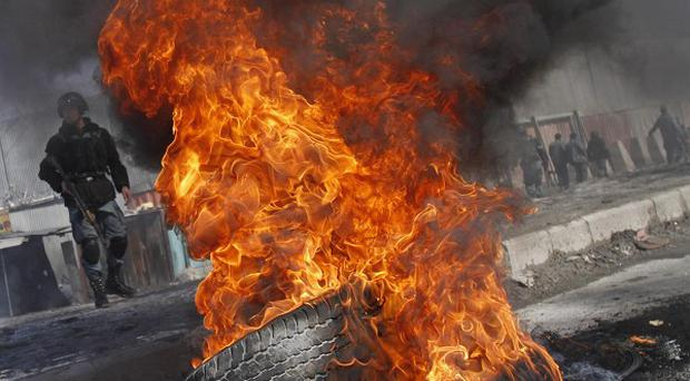 Tyres are set on fire during an anti-US demonstration in Kabul, Afghanistan (AP)