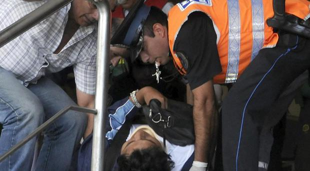 A policeman helps carry a wounded passenger from a commuter train after a crash in Argentina (AP)