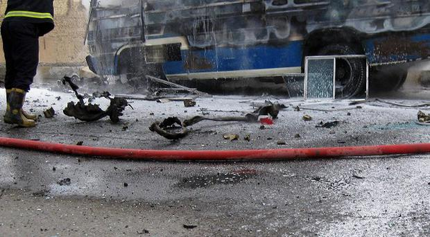 Iraqi firefighters try to extinguish a burning bus at the scene of a car bomb explosion in Baghdad (AP)