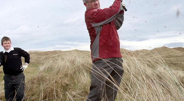 Northern Ireland Environment Minister Alex Attwood plays golf on the site of the proposed new Bushmills Dunes golf course
