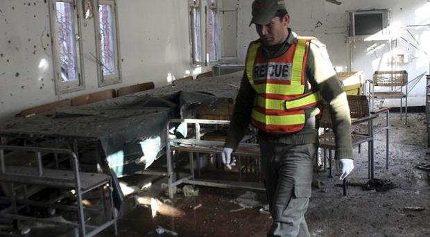 A rescue worker at a police station targeted by suicide attackers in Peshawar (AP)