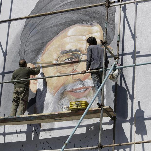 An Iranian mural artist paints a portrait of supreme leader Ayatollah Ali Khamenei, who controls the country's nuclear programme(AP)