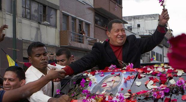 Venezuela's president Hugo Chavez greets supporters while travelling from Miraflores to Caracas, Venezuela (AP/Ariana Cubillos)