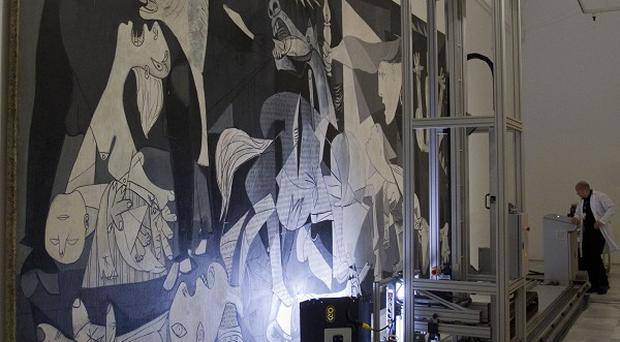 A technician works as a camera mounted on a mobile robot-like structure moves across Pablo Picasso's 'Guernica' painting (AP/Paul White)