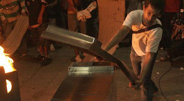 A demonstrator destroys turnstiles during riots at a railway station in Buenos Aires, Argentina (AP/Alberto Raggio, DyN)