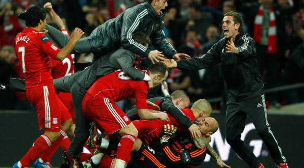 LONDON, ENGLAND - FEBRUARY 26: Goalkeeper Jose Reina of Liverpool is mobbed by team mates as they celebrate their penalty shoot out victory after the Carling Cup Final match between Liverpool and Cardiff City at Wembley Stadium on February 26, 2012 in London, England. Liverpool won 3-2 on penalties. (Photo by Paul Gilham/Getty Images)