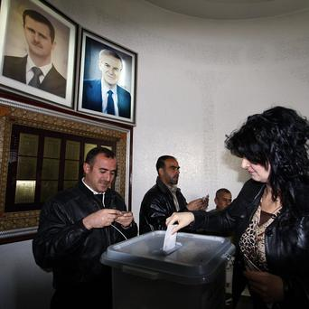 A woman casts her referendum vote under the portraits of Syrian President Bashar Assad, left, and his father Hafez Assad (AP)