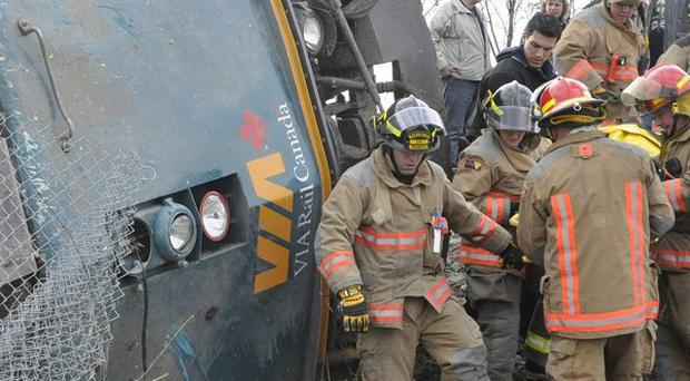 Emergency crews help extract Via Rail employees from a derailed train carriage in Burlington, Ontario (AP/The Canadian Press, David Ritchie)