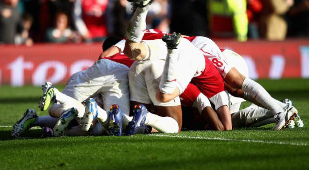 LONDON, ENGLAND - FEBRUARY 26: Theo Walcott of Arsenal is mobbed by team mates after scoring his second goal during the Barclays Premier League match between Arsenal and Tottenham Hotspur at Emirates Stadium on February 26, 2012 in London, England. (Photo by Clive Mason/Getty Images)