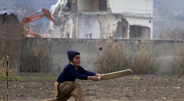 Pakistani youngsters play cricket near the compound of Osama bin Laden which was demolished by authorities in Abbottabad (AP)