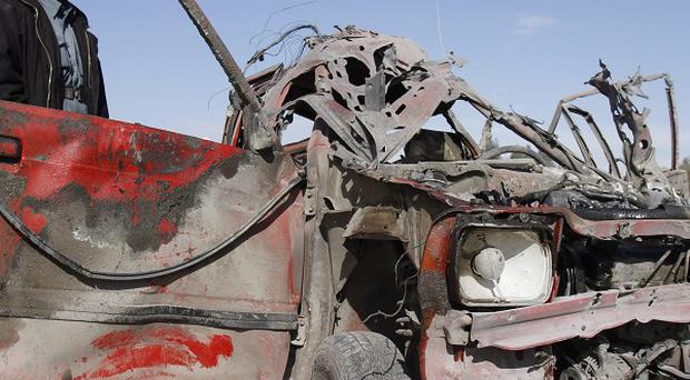An police officer inspects a vehicle destroyed in the bomb blast in Jalalabad, Afghanistan (AP)