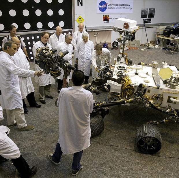 Nasa staff check out a replica of the Mars Science Laboratory rover (AP)