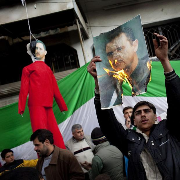 People burn portraits of President Bashar Assad during a demonstration in Idlib, northern Syria (AP)