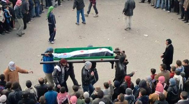 Anti-Syrian regime mourners carry the coffin of a protester killed by security forces in Idlib (AP)