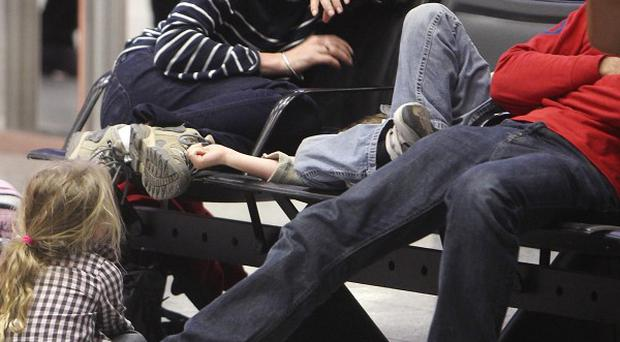 Passengers rest in a terminal amid a new three-day strike by workers involved in a long-running dispute at Frankfurt airport (AP)