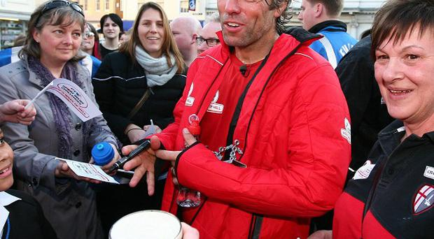 John Bishop is mobbed by fans after crossing the finishing line in Faversham, Kent