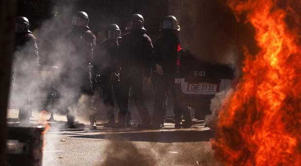 Riot police look on as rubbish containers burn during clashes following a demo in Barcelona (AP)