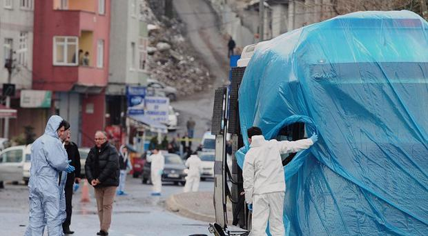 Forensic police cover a damaged vehicle after a bomb went off in Istanbul (AP)