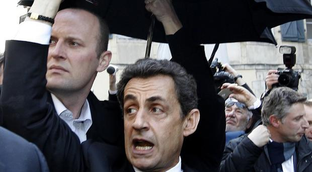 French President Nicolas Sarkozy waves as he enters his car surrounded by security staff in Bayonne(AP)