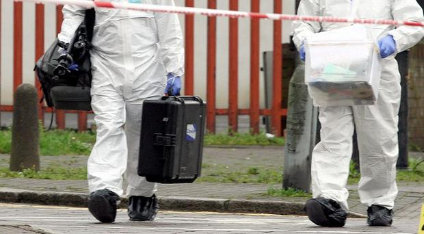 Police forensic experts examine the scene in Belfast city centre after a man was shot dead