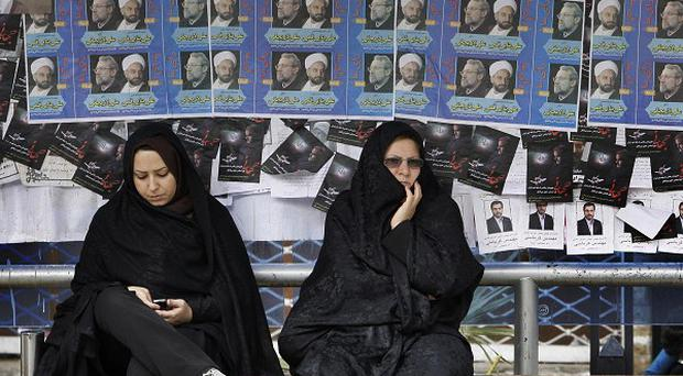 Iranian women sit at a bus stop in front of parliamentary election campaign posters (AP)