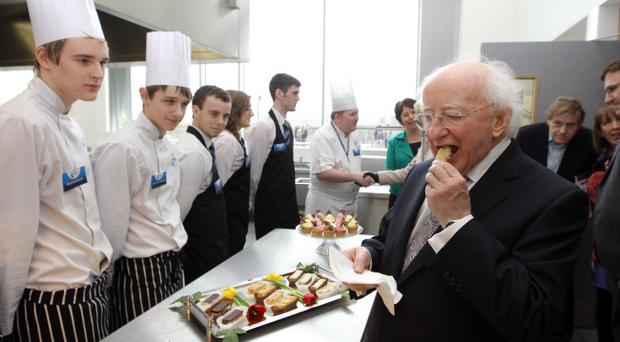 Irish President Michael D Higgins tastes a fish goujon served up at Belfast Metropolitan College's Titanic Quarter campus yesterday during his first official visit to the city