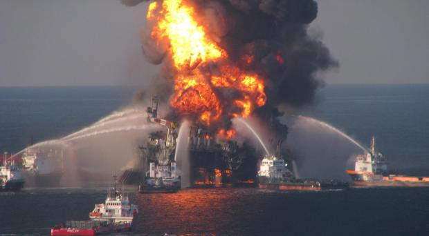 FILE - In this April 21, 2010 file photo provided by the U.S. Coast Guard, fire boat response crews spray water on the blazing remnants of BP's Deepwater Horizon offshore oil rig. BP agreed late Friday March 2, 2012 to settle lawsuits brought by more than 100,000 fishermen who lost work, cleanup workers who got sick and others who claimed harm from the oil giant's 2010 Gulf of Mexico disaster, the worst offshore oil spill in the nation's history. The momentous settlement will have no cap to compensate the plaintiffs, though BP PLC estimated it would have to pay out about $7.8 billion, making it one of the largest class-action settlements ever. After the Exxon Valdez disaster in 1989, the company ultimately settled with the U.S. government for $1 billion, which would be about $1.8 billion today. (AP Photo/US Coast Guard, File)