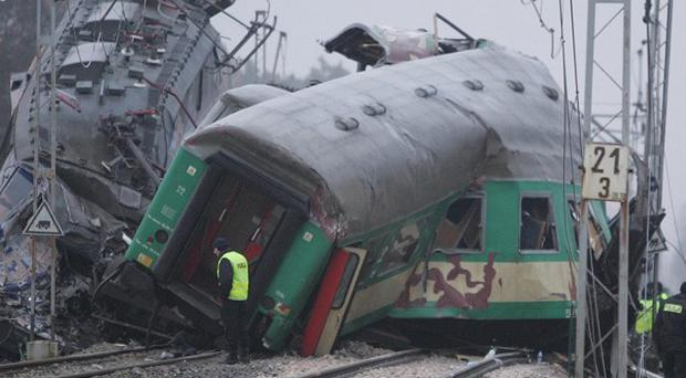 Rescuers at the scene where two trains crashed head-on in southern Poland (AP)