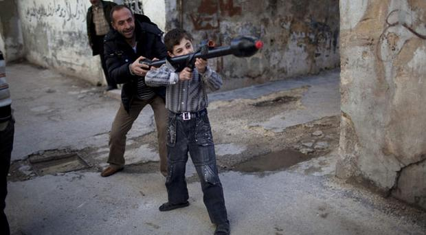 A man teaches Bilal, 11, how to use a toy rocket propelled grenade in Idlib, north Syria, Sunday, March 4, 2012. (AP Photo/Rodrigo Abd)