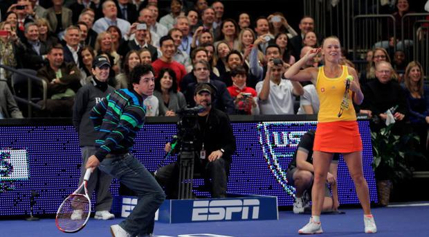 NEW YORK, NY - MARCH 05: Golfer Rory McIlroy of Northern Ireland joins his girlfriend Caroline Wozniacki of Denmark on the court and returns against Maria Sharapova of Russia during the BNP Paribas Showdown at Madison Square Garden on March 5, 2012 in New York City. (Photo by Chris Trotman/Getty Images)
