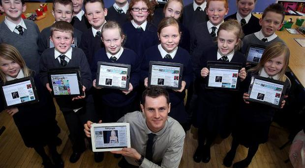 P6 Schoolkids from Cliftonville Primary School pictured with iPads which they use in class and Thomas Hawkins the Belfast Telegraph iPad Journalist