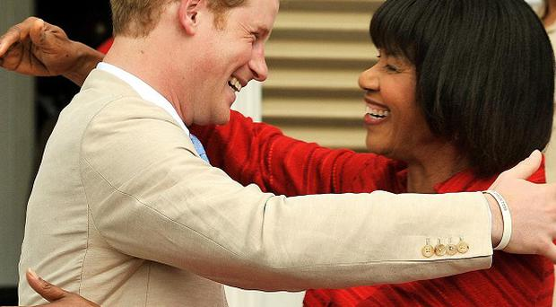 Prince Harry embraces the prime minister of Jamaica Portia Simpson Miller after he arrived at Devon Hall