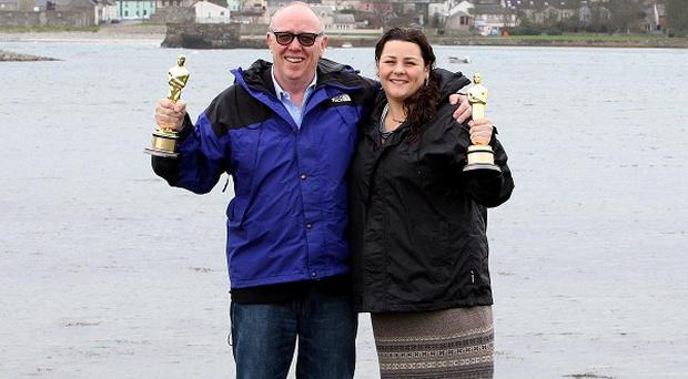 Oscar winner Terry George with his daughter Oorlagh holding their Oscars, at Coney Island in Co Down, where his film The Shore was shot