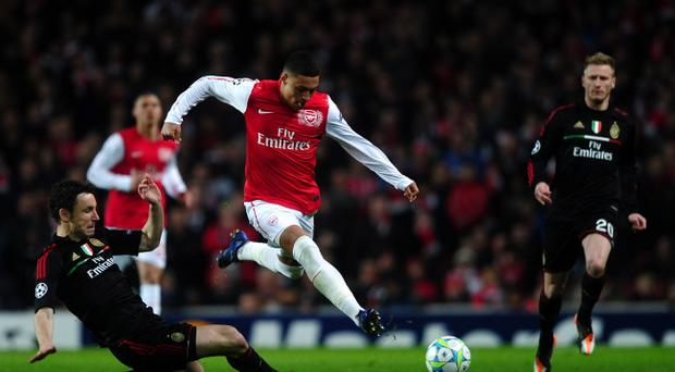 LONDON, ENGLAND - MARCH 06: Alex Oxlade-Chamberlain of Arsenal leaps over the tackle of Mark van Bommel of AC Milan during the UEFA Champions League Round of 16 second leg match between Arsenal and AC Milan at Emirates Stadium on March 6, 2012 in London, England. (Photo by Laurence Griffiths/Getty Images)