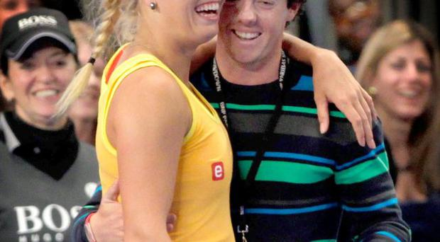 Golfer Rory McIlroy of Northern Ireland joins his girlfriend Caroline Wozniacki of Denmark on the court during her match against Maria Sharapova of Russia at the BNP Paribas Showdown at Madison Square Garden on March 5, 2012 in New York City.