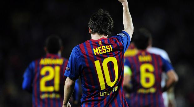 FC Barcelona's Lionel Messi from Argentina, centre, reacts after scoring his third goal against Bayer 04 Leverkusen during a Champions League round of sixteen, second leg, soccer match at the Nou Camp, in Barcelona, Spain, Wednesday, March 7, 2012