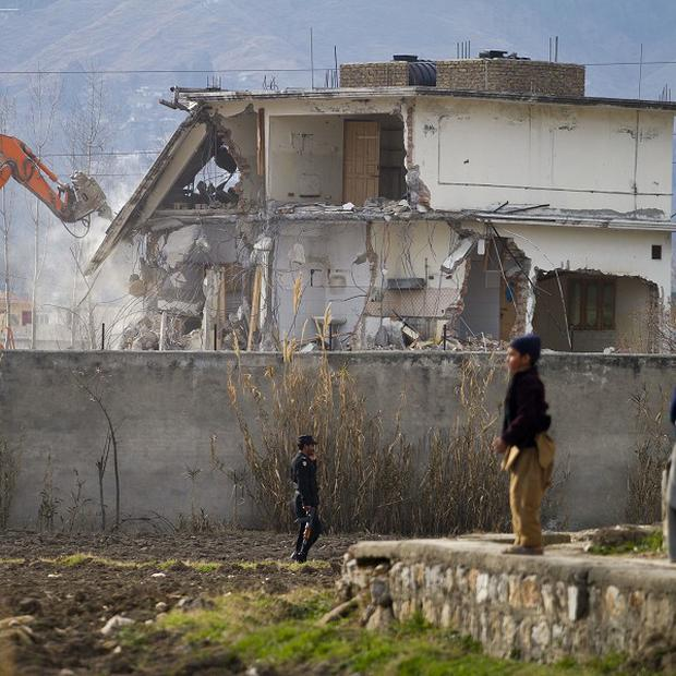 A police commando stands guard as authorities use heavy machinery to demolish Osama bin Laden's compound in Abbottabad(AP)
